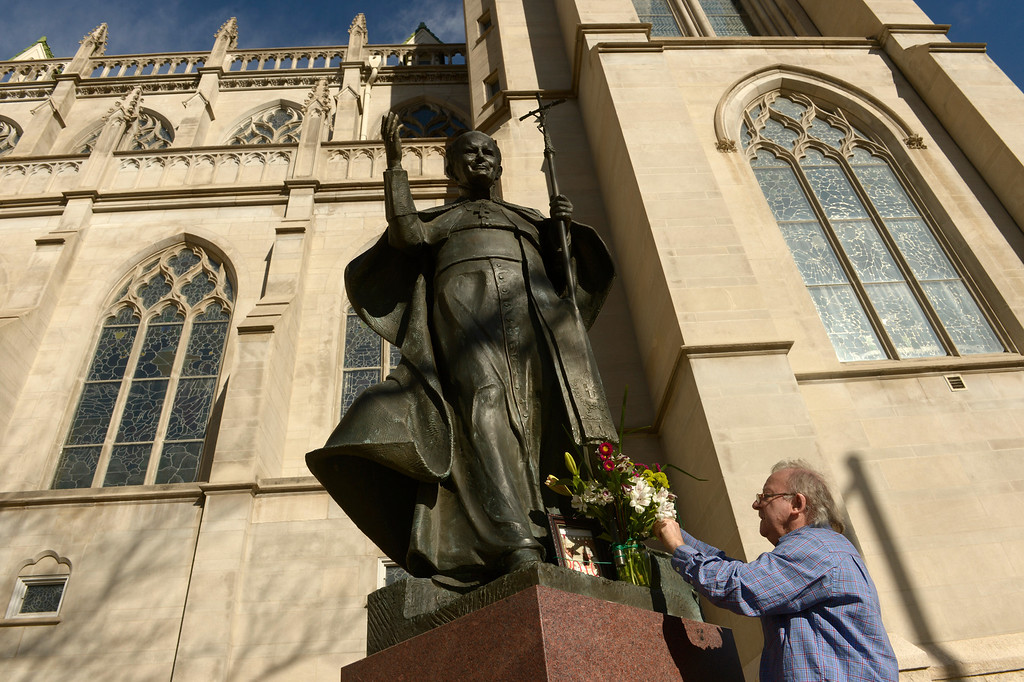 . DENVER, CO- MARCH 13:   Ryszard Drubkowski puts flowers on the statue of Pope John Paul II before an afternoon mass that was held at the Cathedral Basilica of the Immaculate Conception in Denver, CO on March 13th, 2013 after the announcement of the new pope. Jorge Mario Bergoglio, who will be called Francis, will be the 266th pontiff of the Roman Catholic Church. He is also the first non-European pope in more than 1,200 years and the first member of the Jesuit order to lead the church. (Photo By Helen H. Richardson/ The Denver Post)