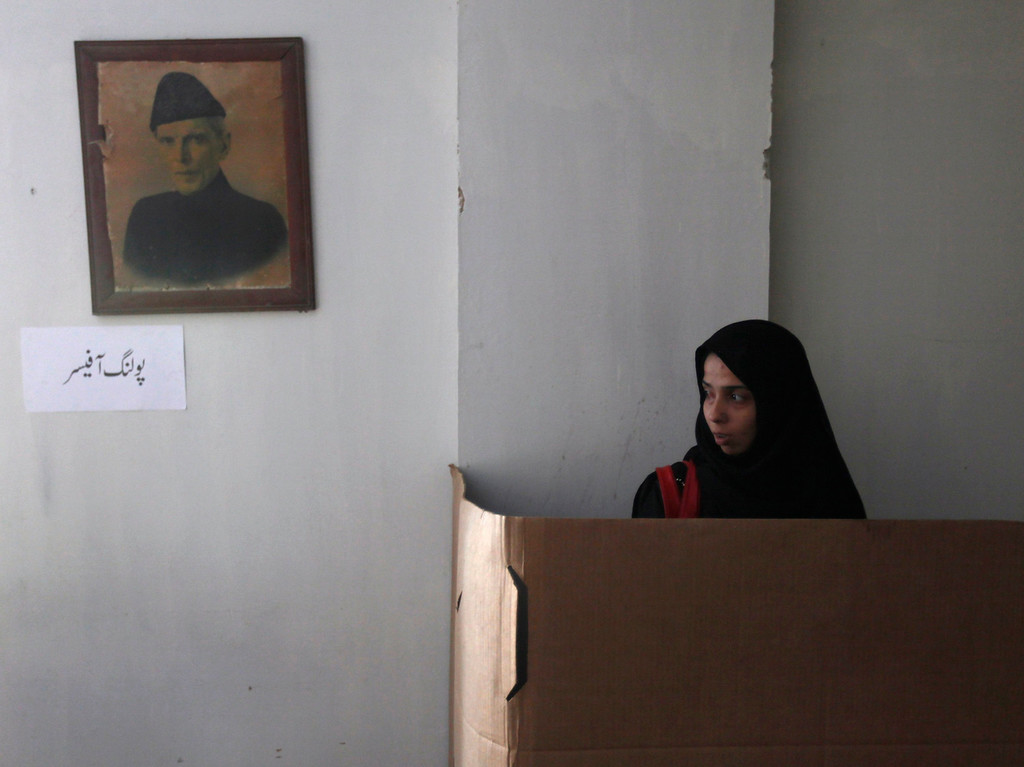 """. A female voter stamps a ballot paper at a polling booth inside a polling station in Karachi May 11, 2013. A string of militant attacks cast a long shadow over Pakistan\'s general election on Saturday, but millions still turned out to vote in a landmark test of the troubled country\'s democracy. A picture of Mohammad Ali Jinnah, founder and first governor-general of Pakistan hangs on the wall. The words on the sign on left read in Urdu as \""""polling officer\"""". REUTERS/Akhtar Soomro"""