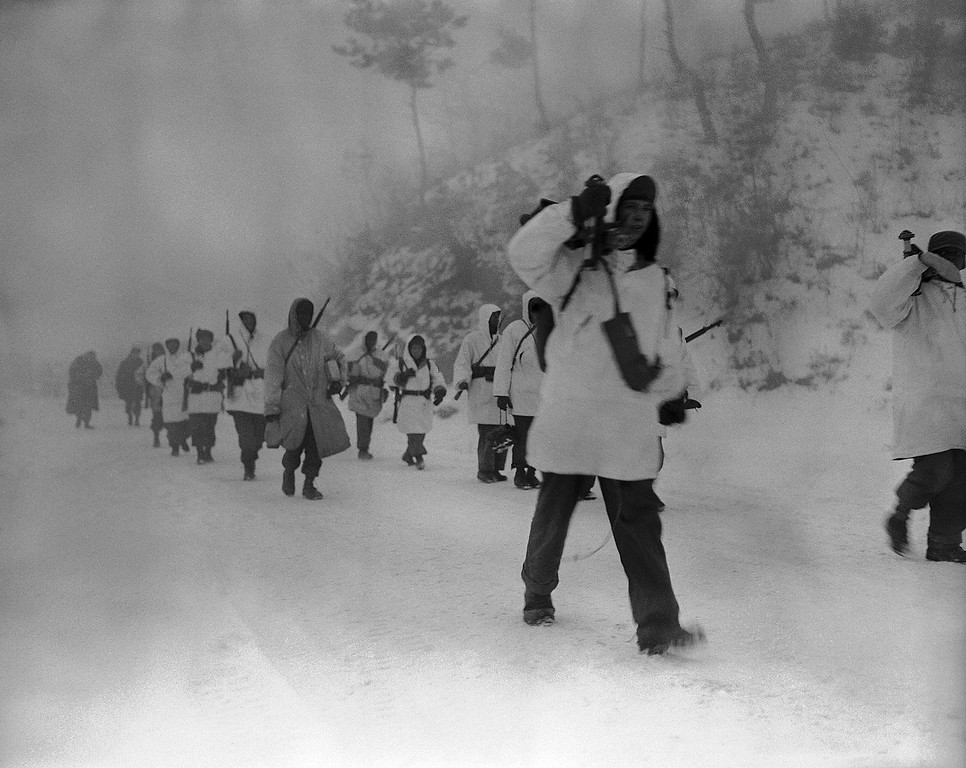 . A mantle of fresh snow helps obscure parka-clad Allied infantrymen as they approach Wonju in forced march on the battered Korean city on Jan. 23, 1951. Allied forces advanced five miles north of Wonju after an earlier withdrawal from the see-saw rail hub. (AP Photo/Max Desfor )
