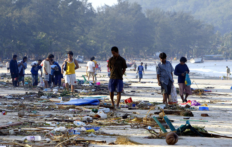 . People walk through debris along the shoreline of Pathong beach of Phuket island, southern Thailand, 27 December 2004, a day after a tidal wave devastated the coastline.  The death toll 27 December from a massive 9.0 magnitude earthquake off Indonesia and tsunamis that it unleashed reached over 14,00, almost 400 in Thailand alone, with officials reporting deaths in seven countries in southern and southeastern Asia. SAEED KHAN/AFP/Getty Images