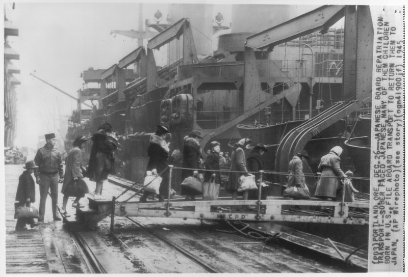 """""""Japanese Board Repatriation Transport -- Sober faced Japanese, many of them children born in U.S., file aboard transport in Portland, Oregon to return them to Japan.""""--caption on photograph."""