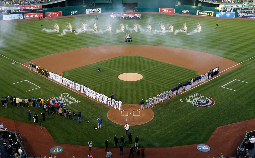. The Oakland Athletics and the Seattle Mariners stand for the signing of the National Anthem during Opening Day at O.co Coliseum on April 1, 2013 in Oakland, California.  (Photo by Ezra Shaw/Getty Images)