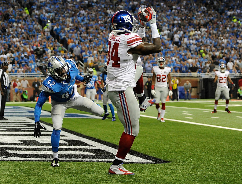 . Larry Donnell #84 of the New York Giants catches a touchdown pass against Isa Abdul-Quddus #42 of the Detroit Lions during the second quarter at Ford Field on September 8, 2014 in Detroit, Michigan. (Photo by Joe Sargent/Getty Images)