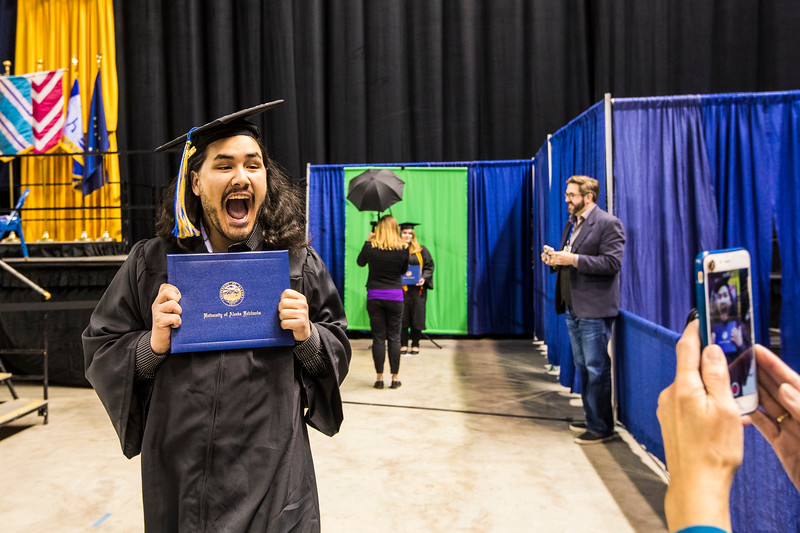 Eugene Franklin Cole III, who earned a bachelor's degree in art, celebrates after walking across the stage during UAF's  commencement ceremony on May 5, 2018, at the Carlson Center.