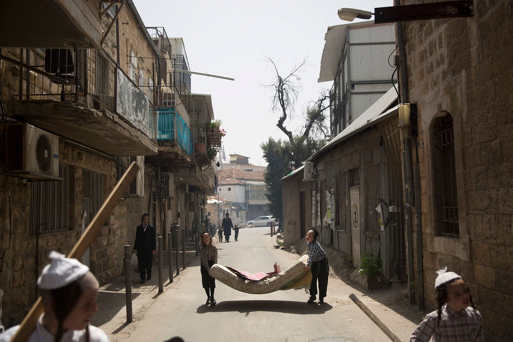 . Ultra-Orthodox Jewish youth carry mattress to be burn with other leavened items in final preparation for the Passover holiday in Jerusalem, Friday, April 22, 2016. Jews are forbidden to eat leavened foodstuffs during the Passover holiday that celebrates the biblical story of the Israelites\' escape from slavery and exodus from Egypt. (AP Photo/Oded Balilty)