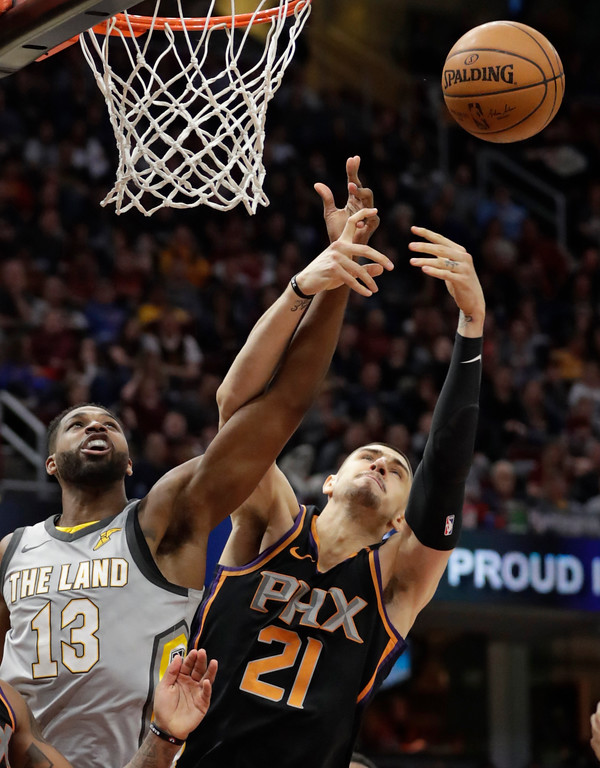 . Cleveland Cavaliers\' Tristan Thompson (13) and Phoenix Suns\' Alex Len (21) vie for a rebound during the second half of an NBA basketball game Friday, March 23, 2018, in Cleveland. The Cavaliers won 120-95. (AP Photo/Tony Dejak)