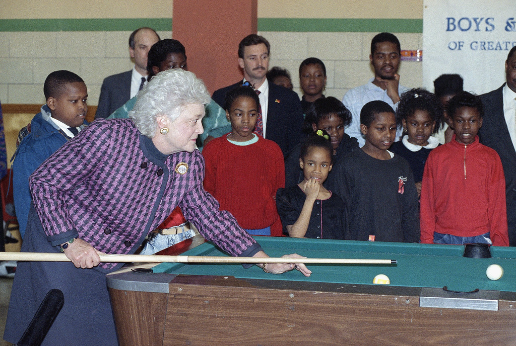 . First Lady Barbara Bush, left, takes a stab at pool as she visits with elementary students at the game room of the Boys and Girls Club, Tuesday, Feb. 27, 1990, Southeast Washington, D.C. The kids are unidentified. (AP Photo/Dennis Cook)