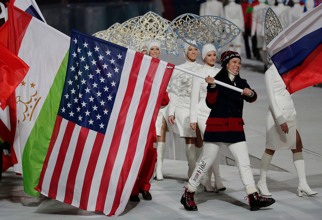 . United States\' Julie Chu carries her nation\'s flag while participating in the closing ceremony of the 2014 Winter Olympics, Sunday, Feb. 23, 2014, in Sochi, Russia. (AP Photo/Charlie Riedel)