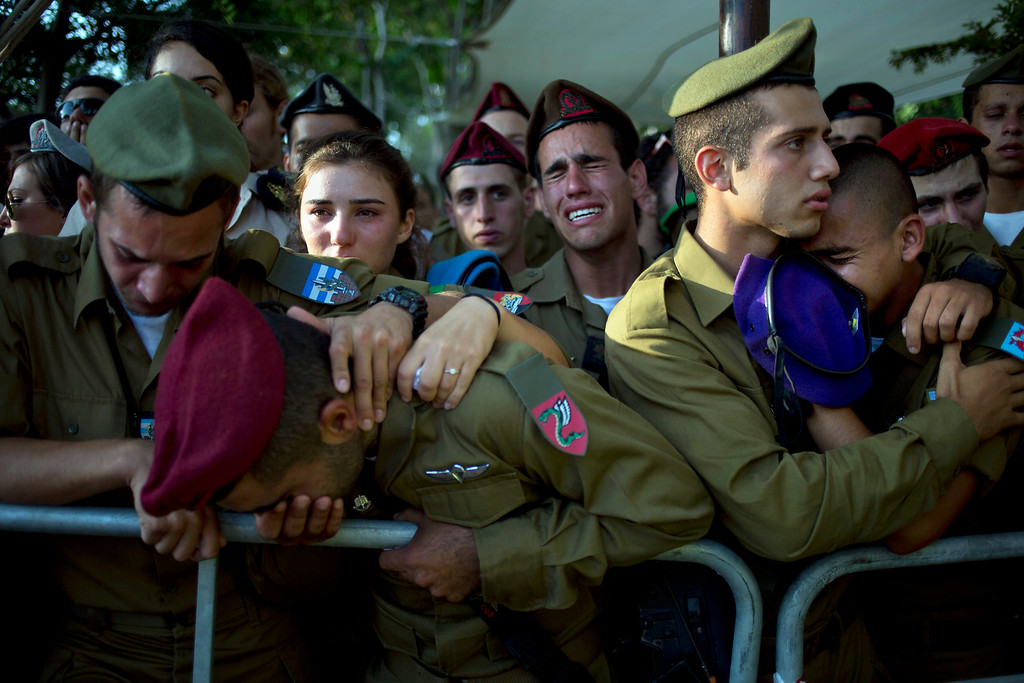""". Israeli soldiers mourn over the grave of Sergeant Sagi Erez, an infantry soldier training to be a squad commander, during his funeral at the military cemetery in Haifa, northern Israel, Tuesday, July 29, 2014. Erez, 19, was killed in combat after Gaza militants used a tunnel to sneak into Israel.  Israeli Prime Minister Benjamin Netanyahu said Monday that Israel must be ready for a \""""prolonged\"""" military operation in the Gaza Strip. (AP Photo/Ariel Schalit, File)"""