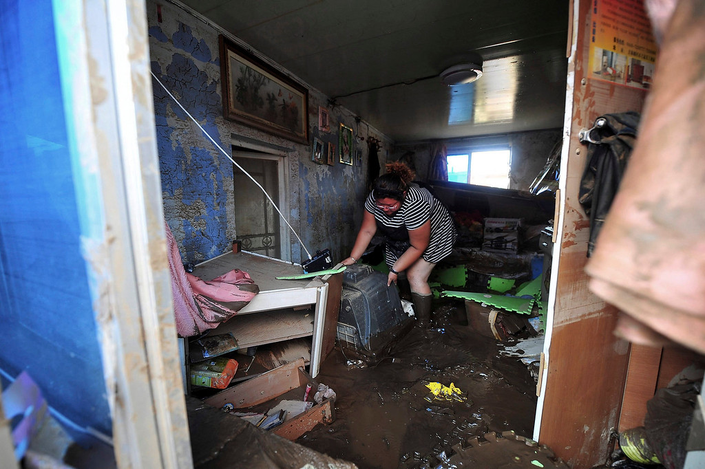 . A woman cleans her house after flood waters sweept through the Nankouqian town in Fushun in northeast China\'s Liaoning province on Sunday, Aug. 18, 2013. In China\'s northeast, separate flooding has affected millions of people, with torrential downpours Saturday causing the Nei River to overflow near the city of Fushun, sweeping away homes, roads, and utilities and leaving 54 people dead. (AP Photo)