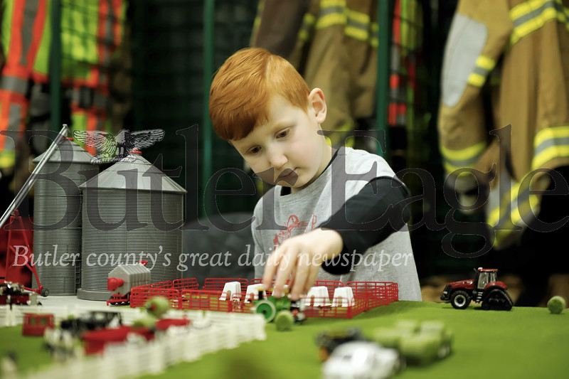 Wyatt McCall, 4, of west Sunbury plays with a model farm at the Butler Fire Department Toy Farm Show Saturday. Seb Foltz/Butler Eagle
