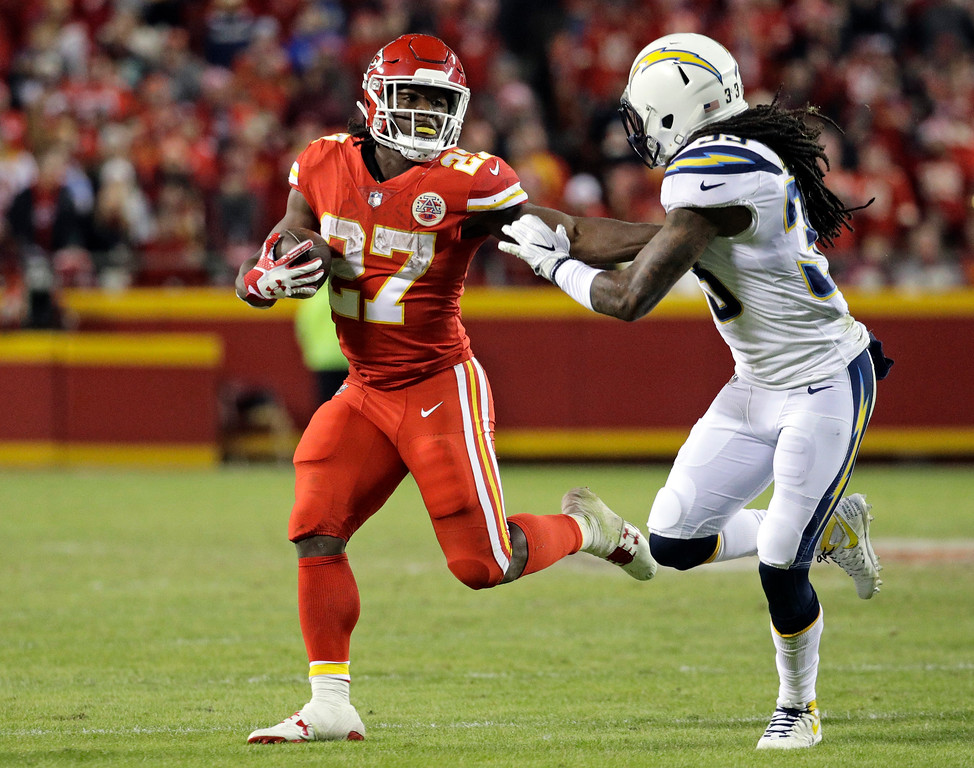 . Kansas City Chiefs running back Kareem Hunt (27) is pursued by Los Angeles Chargers safety Tre Boston (33) during the second half of an NFL football game in Kansas City, Mo., Saturday, Dec. 16, 2017. (AP Photo/Charlie Riedel)