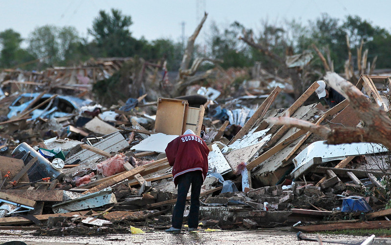 . A local resident allowed looks through the rubble of a destroyed home, one day after a tornado moved through Moore, Okla., Tuesday, May 21, 2013.  Emergency crews searched the broken remnants of an Oklahoma City suburb Tuesday for survivors of a massive tornado that flattened homes and demolished an elementary school. (AP Photo/Brennan Linsley)