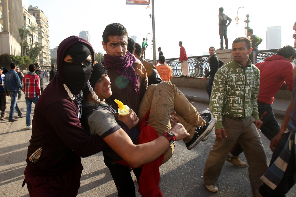 . Protesters evacuate a wounded protester from the scene of clashes in downtown Cairo, Egypt, Saturday, March 9, 2013.  (AP Photo/Mohammed Abu Zaid)
