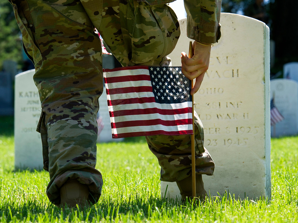 . A member of the Army 3d U.S. Infantry Regiment, The Old Guard, places a flag at the headstone of fallen military member during its annual Flags In ceremony at Arlington National Cemetery, Thursday, May 24, 2018, in Arlington, Va. (AP Photo/Cliff Owen)