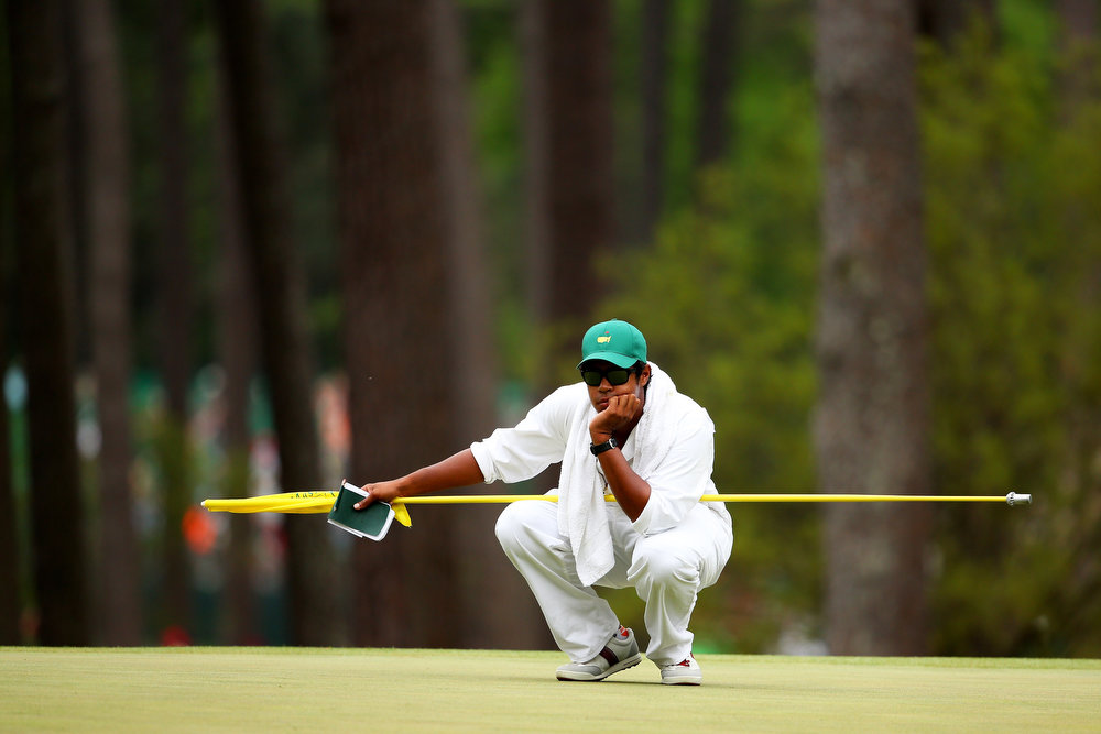 Description of . Qass Singh, the caddie and son of Vijay Singh of Fiji, kneels down on the third hole during the final round of the 2013 Masters Tournament at Augusta National Golf Club on April 14, 2013 in Augusta, Georgia.  (Photo by Mike Ehrmann/Getty Images)