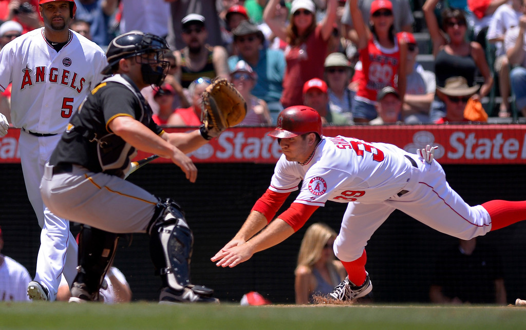 . Los Angeles Angels\' J.B. Shuck, right, scores on a fielder\'s choice by Mike Trout as Pittsburgh Pirates catcher Michael McKenry takes a late throw during the second inning of their baseball game on Sunday, June 23, 2013, in Anaheim, Calif.  (AP Photo/Mark J. Terrill)