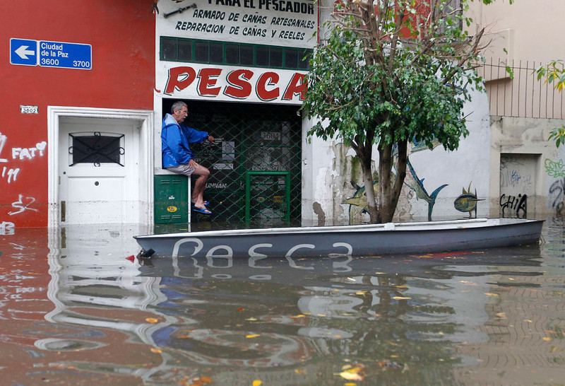 . A man is seen next to a boat in a flooded street after a rainstorm in Buenos Aires April 2, 2013. Thunderstorms damaged property and vehicles, cut power and caused delays on flights in Buenos Aires and its suburbs. The City\'s SAME emergency service announced that the death toll has risen to five.     REUTERS/Enrique Marcarian