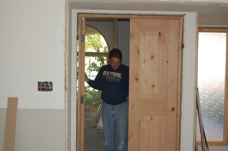 Tom hanging the new doors.