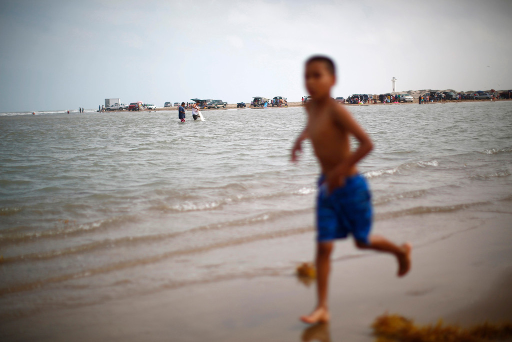 ". A boy runs on the shore at the boundary between the United States and Mexico, where the Rio Grande river meets the Gulf of Mexico in Brownsville, Texas March 31, 2013. Brooks County has become an epicentre for illegal immigrant deaths in Texas. In 2012, sheriff\'s deputies found 129 bodies there, six times the number recorded in 2010. Most of those who died succumbed to the punishing heat and rough terrain that comprise the ranch lands of south Texas. Many migrants spend a few days in a ""stash house\"", such as the Casa del Migrante, in Reynosa, Mexico, and many are ignorant of the treacherous journey ahead. Picture taken March 31, 2013. REUTERS/Eric Thayer"