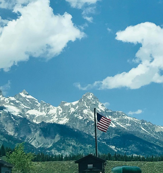 A United States flag is raised by the entrance of the Yellowstone National Park, one of many moments captured by Mary Jane McArdle during a cross-country road trip with her boyfriend, local farmer Warren Shaw.