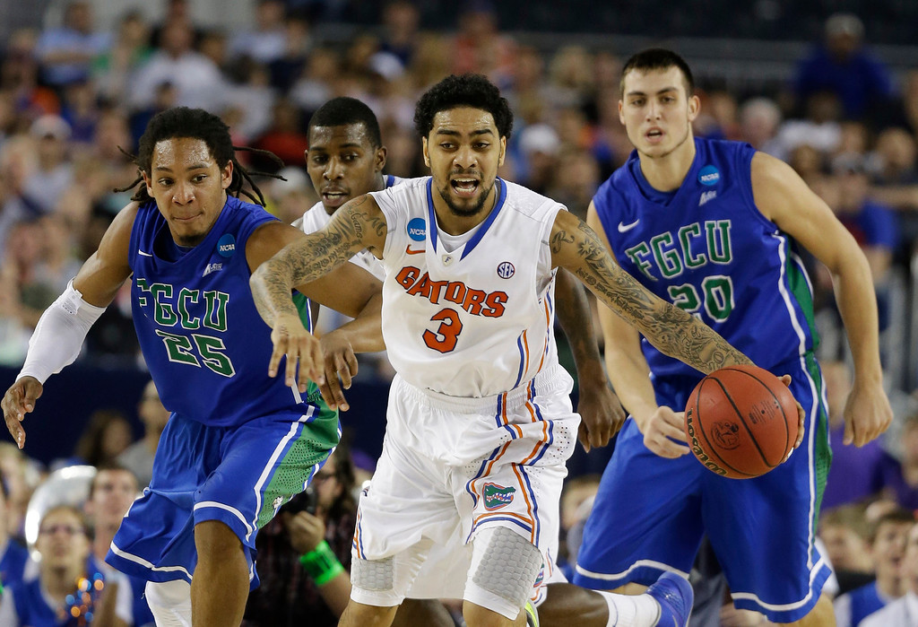 . Florida\'s Mike Rosario (3) is pursued by Florida Gulf Coast\'s Sherwood Brown (25) and Chase Fieler (20) during the first half of a regional semifinal game in the NCAA college basketball tournament, Friday, March 29, 2013, in Arlington, Texas. (AP Photo/David J. Phillip)