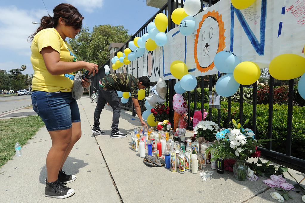 . Jasmine Revelos,17, and Jorge Padilla,17, pay respects at the memorial of their classmate. Students at El Monte High School brought flowers, candles and other items in remembering Adrian Castro, a Senior student who was killed in bus crash in Northern California that took the lives of 10 people. El Monte, CA. 4/13/2014(Photo by John McCoy / Los Angeles Daily News)
