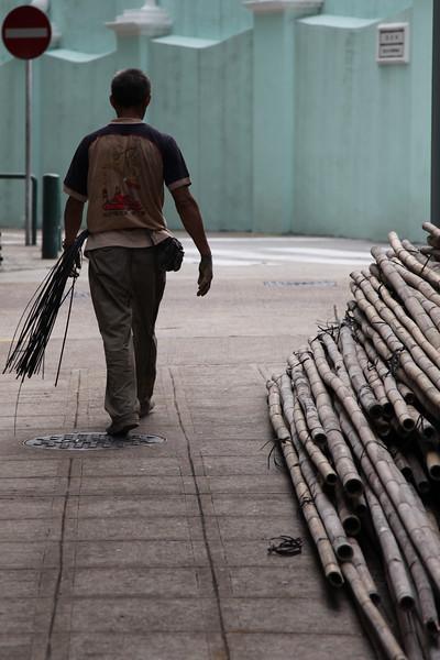Po prawej żerdzie bambusowe, po lewej pan który stawia rusztowania.  To co mu dynda przy pasie sluży do ich montowania, nawet przy budowach najnowczesniejszych i najwyzszych budynkow.