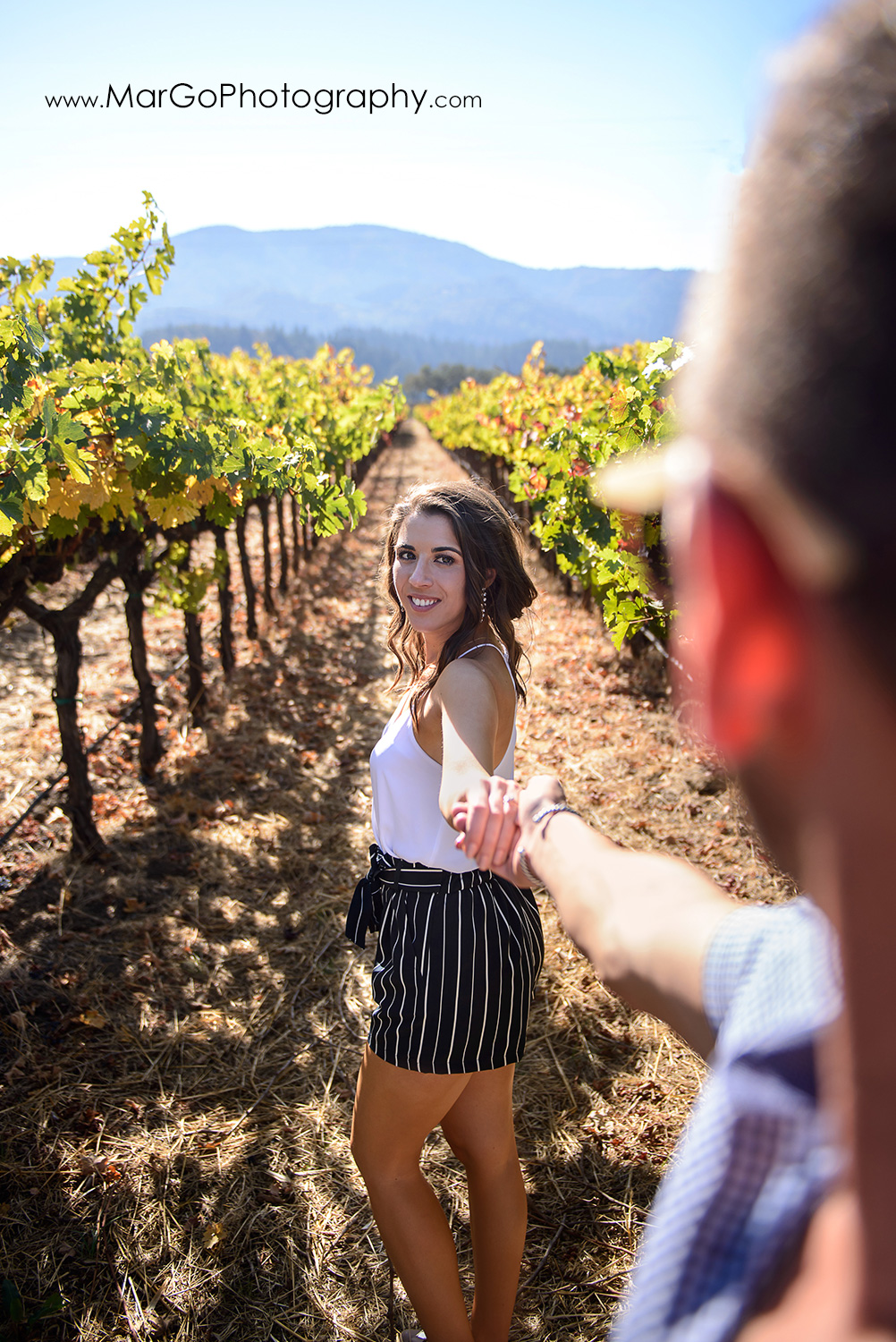 follow me to the vineyard portrait of man in blue shirt led by woman in navy blue shorts and white top during Napa Valley engagement session at Grgich Hills Estate in Rutherford