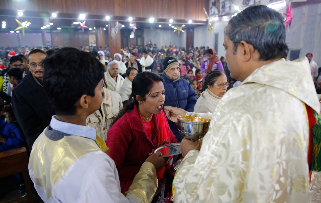. A Christian devotee takes holy communion from a priest after the midnight Christmas mass at Saint Joseph\'s Cathedral on the Christmas eve in Lucknow, India, Monday, Dec. 25, 2017. Though the Hindus and Muslims comprise majority of the population in India, Christmas is a national holiday celebrated with much fanfare. (AP Photo/Rajesh Kumar Singh)