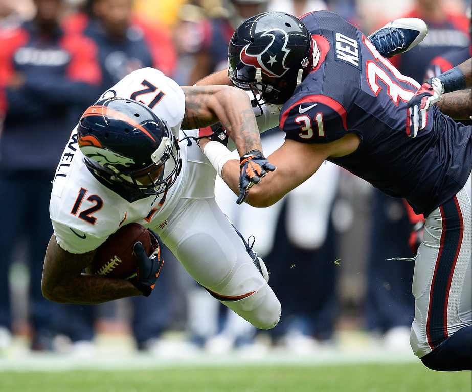 . Denver Broncos wide receiver Andre Caldwell (12) gets upended by Houston Texans free safety Shiloh Keo (31) during the first quarter December 22, 2013 at Reliant Stadium. (Photo by John Leyba/The Denver Post)