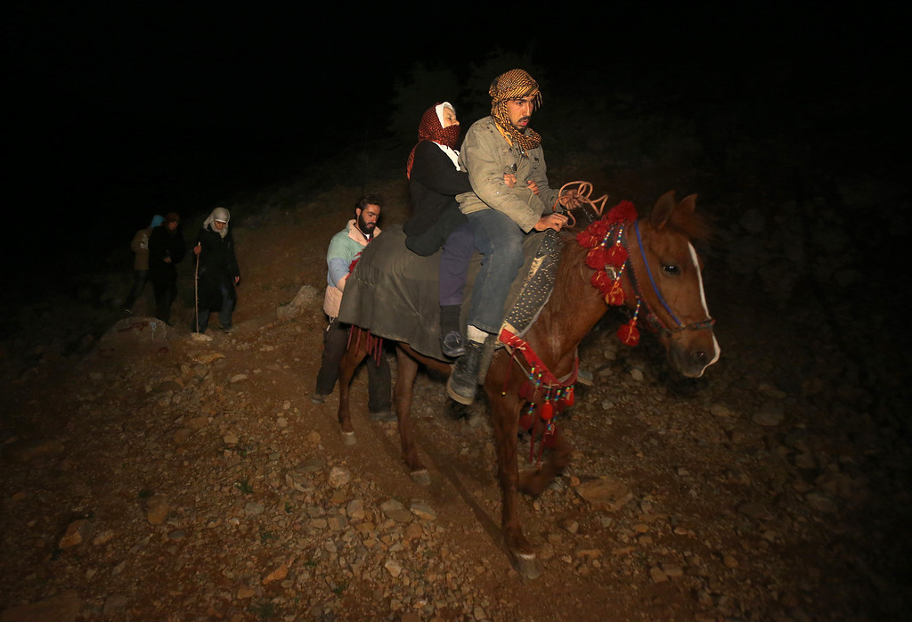 . In this picture taken on early Sunday April 20, 2014, Farizeh Kabalan, 74, who fled her home in the Syrian village of Beit Jinn near the Israeli-occupied Golan Heights, is carried on horseback by a Syrian rider after descending from the 2,814-meter (9,232-foot) Mount Hermon (Jabal el-Sheikh), into the town of Chebaa town in southeast Lebanon. Once at a Lebanese Army checkpoint, Kabalan collapsed into the hands of four Red Cross workers, who loaded her into an ambulance. (AP Photo/Hussein Malla)