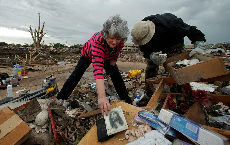 . Lea Bessinger salvages a picture of Jesus as she and her son Josh Bessinger sort through the rubble of the elder Bessinger\'s tornado-ravaged home Tuesday, May 21, 2013, in Moore, Okla. A huge tornado roared through the Oklahoma City suburb Monday, flattening an entire neighborhoods and destroying an elementary school with a direct blow as children and teachers huddled against winds. (AP Photo/Charlie Riedel)