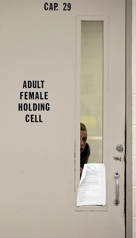 . A detainee looks through the door of a holding cell at a U.S. Customs and Border Protection processing facility, Wednesday, June 18, 2014, in Brownsville,Texas.  (AP Photo/Eric Gay, Pool)