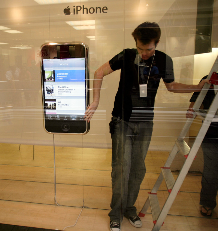 . An Apple employee steadies the display of the much-ballyhooed Apple  iPhone after bumping into the model while pulling down blackout papers placed over the windows of the Apple store in the tony Cherry Creek Mall in east Denver on Friday, June 29, 2007.  Some of the purchasers spent hours in line for a chance to get the much-ballyhooed phone. (AP Photo/David Zalubowski)