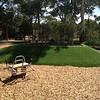 spring rocker in mulch with artificial turf mound and garden bed