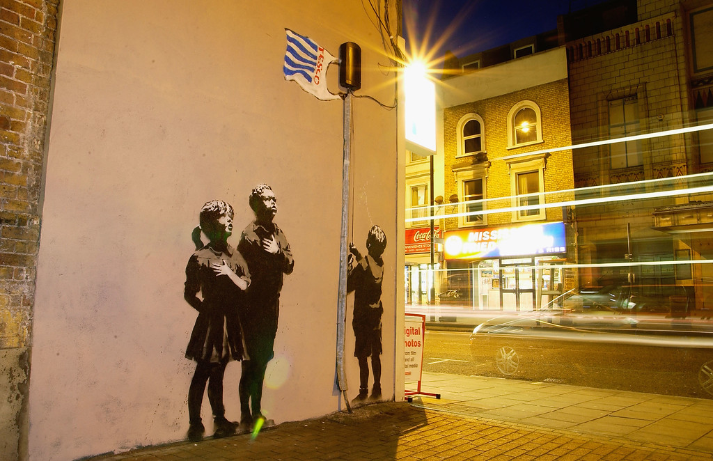 . Artwork in North London, attributed to guerrilla graffiti artist Banksy, is pictured on Essex Road in Islington on March 4, 2008 in London, England. The scene depicts children gathering around a flagpole topped by a Tesco carrier bag. (Photo by Jim Dyson/Getty Images)