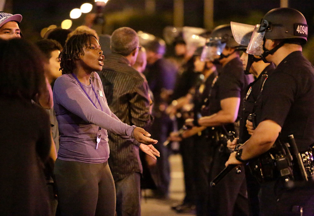 . A protester (L) talks with Los Angeles Police officers as they try to remove protesters from the intersection of Exposition and Crenshaw boulevards, following the George Zimmerman verdict in Los Angeles, California, July 13, 2013. A Florida jury acquitted Zimmerman on Saturday for the shooting death of unarmed black teenager Trayvon Martin, setting free a man who had become a polarizing figure in the national debate over racial profiling and self-defense laws. REUTERS/Jason Redmond