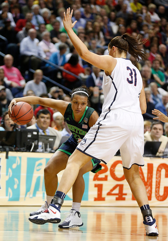. Notre Dame guard Kayla McBride (21) moves by Connecticut center Stefanie Dolson (31) during the first half of the championship game in the Final Four of the NCAA women\'s college basketball tournament, Tuesday, April 8, 2014, in Nashville, Tenn. (AP Photo/John Bazemore)