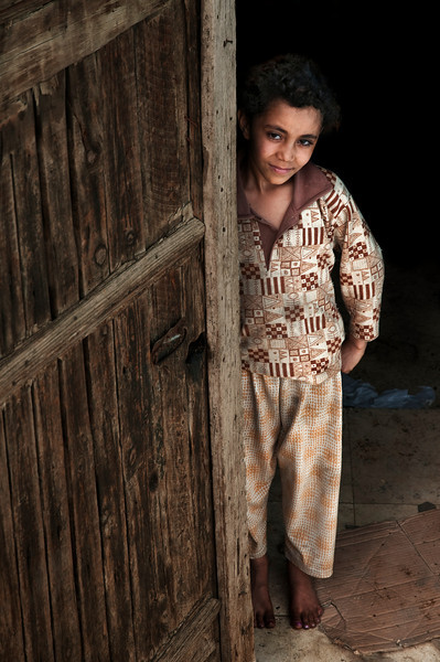 This little girl, like many other Cairo inhabitants, lives in poverty. Her house is located wall to wall with one of Cairo's finest mosques, the Mohammed Ali. Thousands of people walk past her front door every day, most indifferent to her predicament.  Cairo, Egypt 2010.