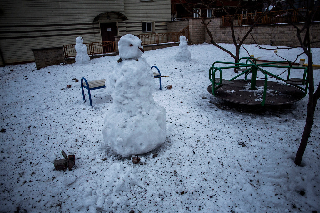 . Snowmen hit by shrapnel and debris are seen in a deserted playground in the Voroshilovsky area,  in the center of Donetsk, Ukraine. Sunday, Jan. 18, 2015. The separatist stronghold, Donetsk, was shaken by intense outgoing and incoming artillery fire as a bitter battle raged for control over the city\'s airport. Streets in the city, which was home to 1 million people before unrest erupted in spring, were completely deserted and the windows of apartments in the center rattled from incessant rocket and mortar fire. (AP Photo/Manu Brabo)