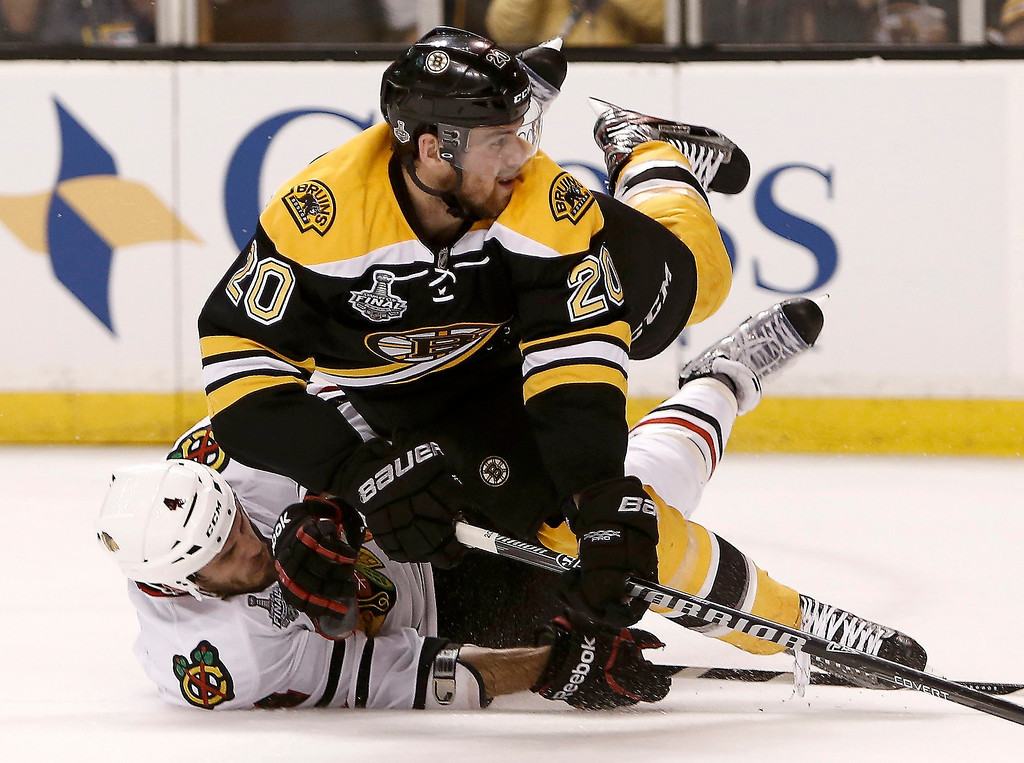 . Boston Bruins left wing Daniel Paille (20) is taken off the puck by Chicago Blackhawks defenseman Niklas Hjalmarsson (4) in the second period during Game 3 of their NHL Stanley Cup Finals hockey series in Boston, Massachusetts, June 17, 2013.  REUTERS/Winslow Townson