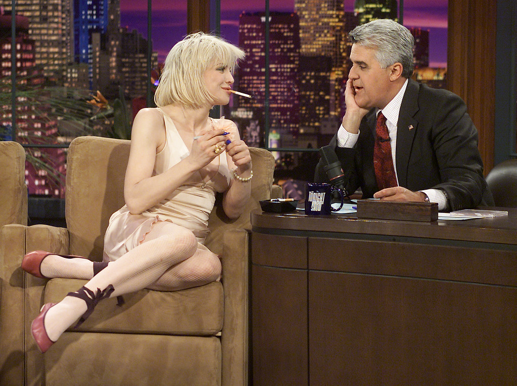 ". Rocker Courtney Love talks with host Jay Leno while making her first appearance on ""The Tonight Show with Jay Leno,\"" Thursday, April 15, 2004, in Burbank, Calif. During the show, Love discussed her recent legal troubles, her image and the tabloids before performing with her band. A judge Thursday ordered Love to stand trial on felony drug charges after hearing testimony alleging that she gave police officers a baggie full of pills. (AP Photo/NBC, Paul Drinkwater)"