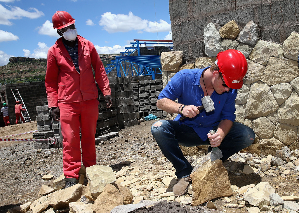 . Prince Harry helps with sandstone cladding for the guardhouse as he visits the construction site for the new Sentebale Mamohato Children\'s Centre at Thaba-Bosiu on December 10, 2014 in Maseru, Lesotho. (Photo by Chris Jackson - WPA Pool /Getty Images)