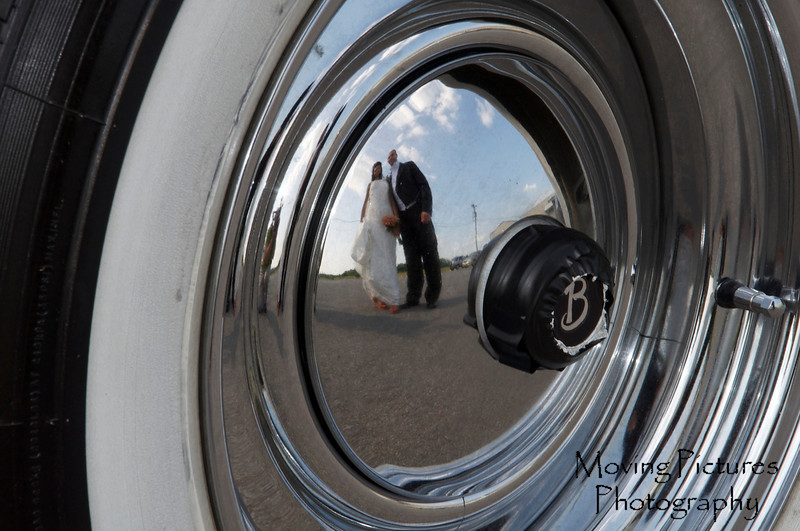 Reflected in the wheel of the Bentley
