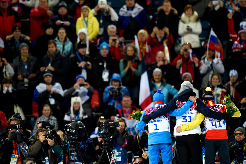 . (R--L) Silver medalist Erik Lesser of Germany, gold medalist Martin Fourcade of France and bronze medalist Evgeniy Garanichev of Russia celebrate on the podium in front of photographers during the flower ceremony for the Men\'s Individual 20 km during day six of the Sochi 2014 Winter Olympics at Laura Cross-country Ski & Biathlon Center on February 13, 2014 in Sochi, Russia.  (Photo by Lars Baron/Getty Images)