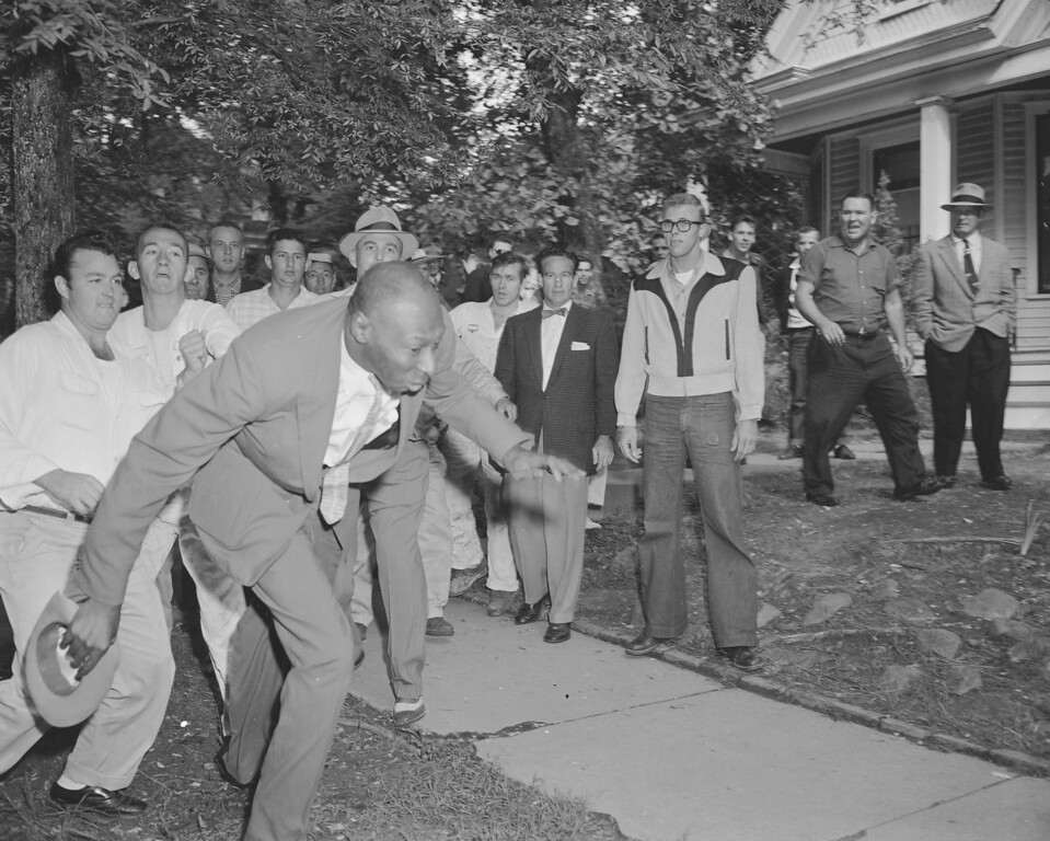 . A reporter from the Tri-State Defender, Alex Wilson, is shoved by an angry mob of white people near Central High School in Little Rock, Ark., Sept. 23, 1957.  The fight started when nine black students gained entrance to the school as the Army enforced integration.  (AP Photo)