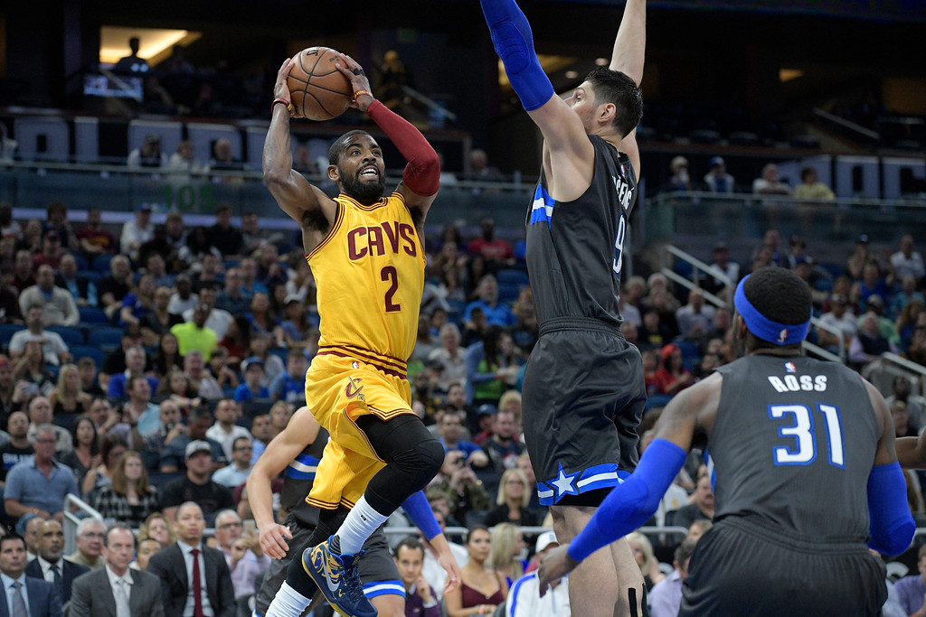 . Cleveland Cavaliers guard Kyrie Irving (2) looks to pass in front of Orlando Magic forward Terrence Ross (31) and center Nikola Vucevic during the first half of an NBA basketball game in Orlando, Fla., Saturday, March 11, 2017. (AP Photo/Phelan M. Ebenhack)