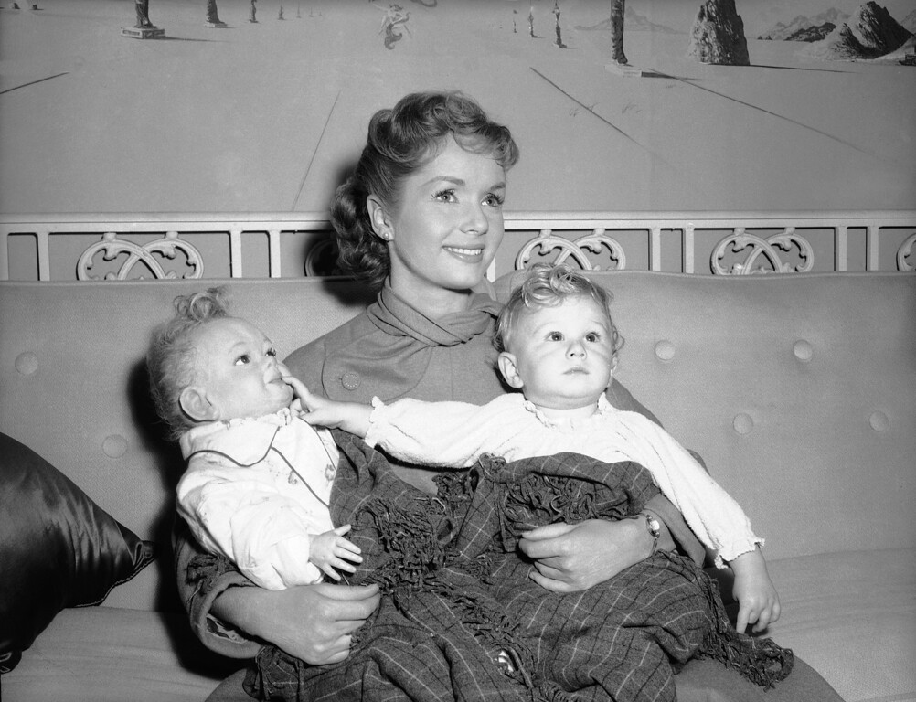 ". Actress Debbie Reynolds on Sept. 5, 1956, has an armful of babies\' but only one is real, year-old Donald Grey, at right. The other is a doll, a stand-in for Donald who plays the title role in a new film, ""Bundle of Joy.\"" Donald\'s doll double is the work of sculptor Jack Young, who modeled the head in clay after several sittings by baby Donald. Welfare rules permit a studio to employ a baby of Donald\'s age only four hours a day. Out of these four hours, the baby can be used before the cameras a total of only two hours. All rehearsing is done with the stand-in doll. Besides, there\'s no holdup for diaper changes. Location unknown. (AP Photo)"