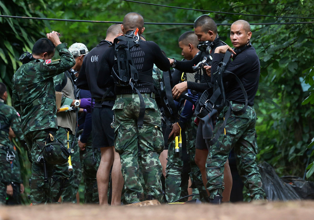. Rescuers prepare dive gear at the entrance of a cave complex where 12 boys and their soccer coach are trapped inside in Mae Sai, Chiang Rai province, in northern Thailand, Wednesday, July 4, 2018. The Thai soccer teammates stranded more than a week in a partly flooded cave said they were healthy on a video released Wednesday, as heavy rains forecast for later this week could complicate plans to safely extract them. (AP Photo/Sakchai Lalit)
